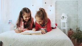 Two friends lying and reading a book. In the background a white wall with glowing lights stock footage