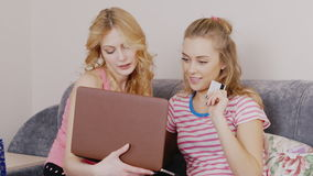 Two friends make a purchase online. Young woman sitting with a laptop on the couch, holding a credit card in the hands stock video footage