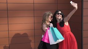 Two friends make a selfie with funny faces. Sunny portrait of girls. beautiful girls in sunglasses with shopping bags in stock video footage