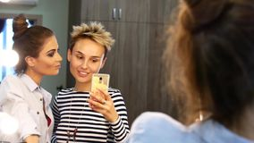 Two friends make a selfie near the mirror. Girls fool around laughing and taking pictures. Two friends make a selfie near the mirror. Girls fool around laughing stock footage