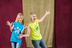 Two friends make silly gestures. For the camera in front of gold curtains Stock Photography