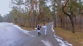 Two friends makes jogging in the morning in winter forest. Young sport people makes morning exercises outdoors. Pretty woman and handsome man wearing sportswear stock video