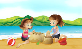 Two friends making a castle at the beach Stock Photo