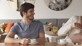 Two friends meet at the cafe. Two attractive young friends meeting at the cafe. Handsome caucasian guy waiting for somebody over the cup of coffee. Pretty stock video footage