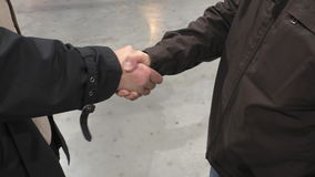 Two friends meeting handshake. Two men wearing outdoor jackets meeting and greeting each other on concrete floor stock video