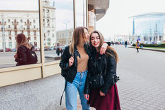 Two friends meeting in the street of the city and hugging . friendship, happiness concept . Couple of women on the street Stock Image