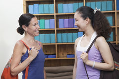 Two friends meeting at the yoga studio, holding bags Stock Images