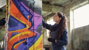 Two friends graffiti painters are drawing abstract images on old damaged column in abandoned house holding aerosol paint. Two friends modern graffiti painters stock video footage