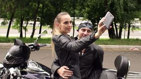 Couple of bikers taking a selfie on a motorcycle. Two friends of motorcyclists in leather jackets doing selfie on phone sitting on a modern motorcycle. Couple stock video footage