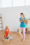 Two friends moving together in a new house Stock Image