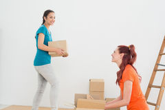 Two friends moving together in a new house Stock Images