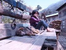 Two friends. Nepalese girl with her sleeping dog in Himalaya mountains Royalty Free Stock Photo