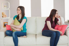 Two friends not talking to each other after fight on the sofa. In sitting room at home stock photography