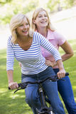 Two friends on one bike outdoors smiling. Looking away from camera Stock Images