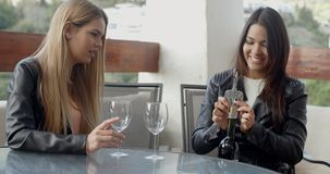 Two friends opening wine bottle. Two young adult female friends in leather jackets opening bottle of wine at table stock footage