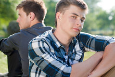 Two friends outdoors back to back. Handsome young men sitting back to back on the field of green grass outdoors on a bright sunny day of spring or summer on Stock Images