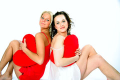 Two friends in pajamas. With pillows in the form of heart Stock Image