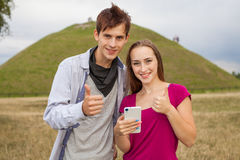 Two friends in a park with mobile phone. Positive emotions Stock Image