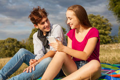 Two friends in a park with mobile phone. Summer time. Royalty Free Stock Photography
