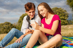 Two friends in a park with mobile phone Royalty Free Stock Photo