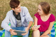 Two friends in park with mobile phone and tablet pc. Royalty Free Stock Images