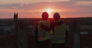 Two friends and partners at construction site on rooftop of building holding each other and looking at amazing sky view. stock video footage