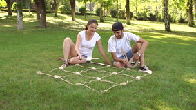 Two friends play to big TIC TAC toe in the Park. stock footage