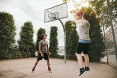 Two friends playing basketball on court. Young men taking jump shot with friend on basketball court. Streetball players having fun on court. Two teenage friends royalty free stock images