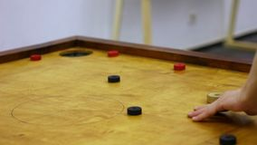 Two friends playing carrom game, strike and pocket table game, family tournament. Stock footage stock video