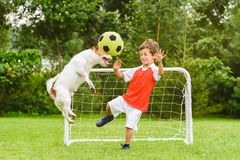 Kid playing football soccer as goalie afraid of ball flying after header shot. Two friends playing football at back yard lawn stock images