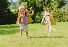 Two friends playing high flyers with cardboard wings. Boy and dog playing plane pilots at sunny lawn Stock Photos