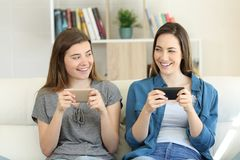 Two friends playing on-line with their smartphones. Two happy friends looking each other ready to play a miltiplayer on-line game with their smartphones at home Royalty Free Stock Photography