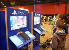Two friends playing PS 4 game consoles. STRASBOURG, FRANCE - MAY 8, 2015: Two friends playing PS 4 game consoles at the open market Digital Game Manga Show Royalty Free Stock Photography