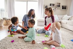 Two friends playing with toddler kids on sitting room floor stock photo