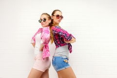 Two friends posing. modern lifestyle.two stylish sexy hipster girls best friends ready for party. Young girl friends Royalty Free Stock Photos