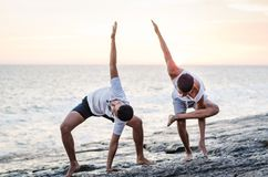 Two friends practicing Yoga on the edge of the ocean at sunset royalty free stock photo