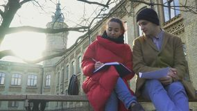 Two friends preparing to exams sitting at the bench in park near university stock video footage