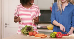 Two friends preparing vegetables. In the kitchen at home stock footage