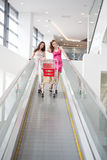 Two friends with purchases on the escalator Royalty Free Stock Image