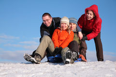 Two friends push two of others on sleighs Royalty Free Stock Photo