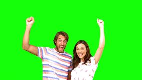 Two friends raising their arms on a green screen. In slow motion stock video