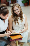 Two friends reading book Stock Images