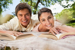 Two friends reading books while lying on a blanket. In the park Royalty Free Stock Photo