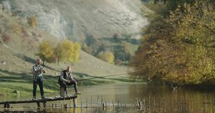 Two friends recreation together at nature , they fishing on lake. stock video footage