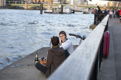 Two friends relaxing on the banks of the Thames. Picnic with win Royalty Free Stock Photography