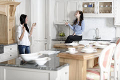 Two friends relaxing in the kitchen Stock Photos