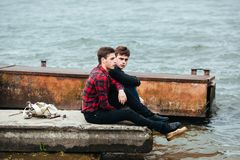 Two friends relaxing on the pier. Stock Photo