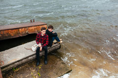 Two friends relaxing on the pier. Royalty Free Stock Image