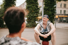 Two friends relaxing after playing basketball on court Stock Photos