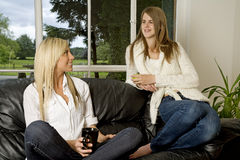 Two friends relaxing on sofa Royalty Free Stock Photo